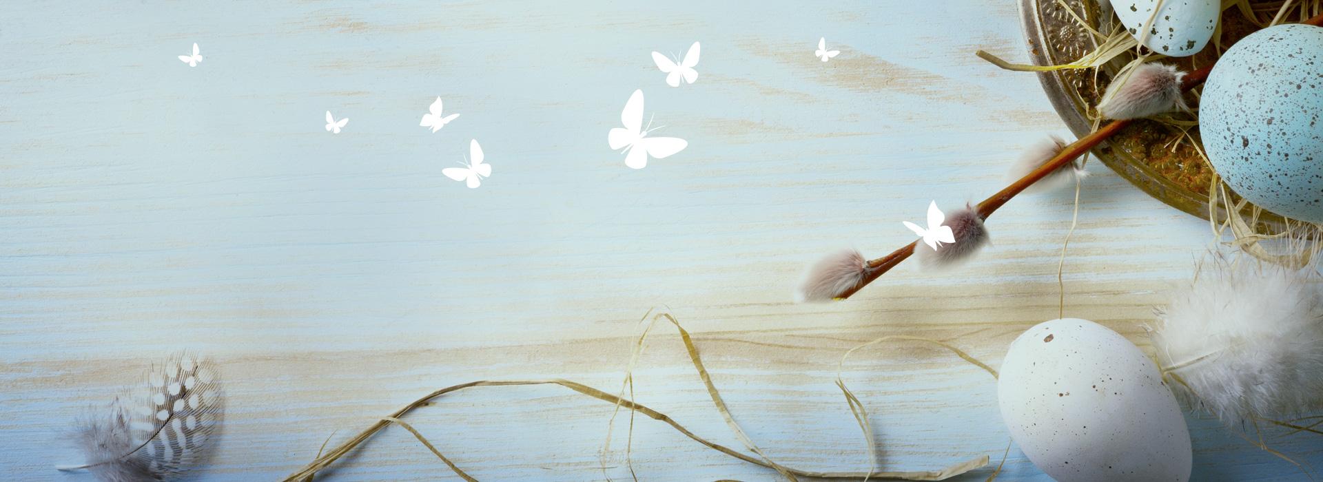 Wir wünschen Ihnen ein frohes Osterfest! Flatternde Schmetterlinge vor österlichem Hintergrund