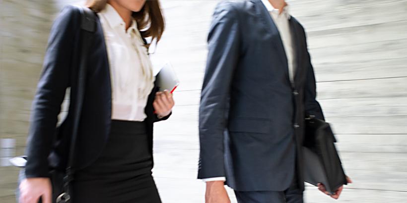 Bild von zwei Business-People, die sich schnell durch ein Bürogebäude bewegen