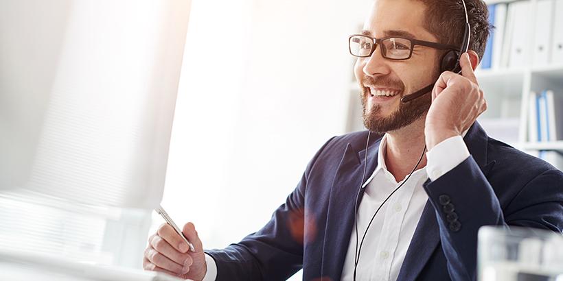 Bild von einem jungen, lächelnden Mann vor dem Bildschirm mit Headset