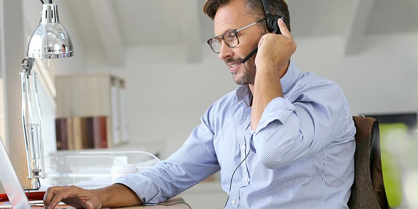 Bild eines Mitarbeiters mit Headset im Homeoffice