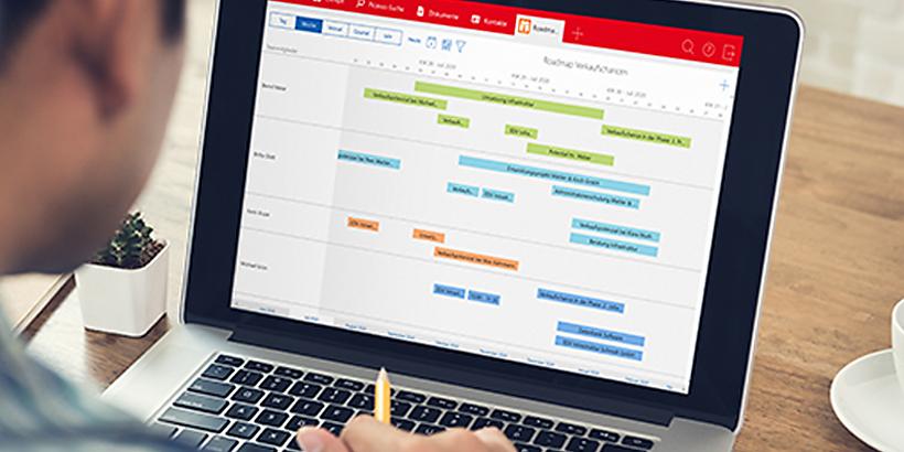 Bild von einem Mann, der vor dem Computer sitzt und sich im Computer einen Projektplan in CAS genesisWorld anschaut