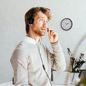 Bild eines am Headset telefonierenden Mannes, der neben seinem Arbeitsplatz steht