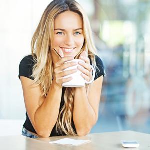 Bild einer jungen Frau beim Kaffeetrinken im Stehen