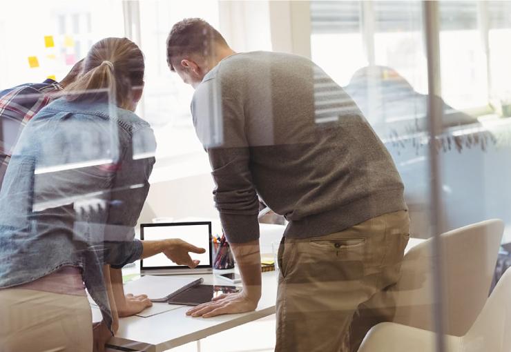 Drei Personen schauen gemeinsam auf ein Tablet und diskutieren.