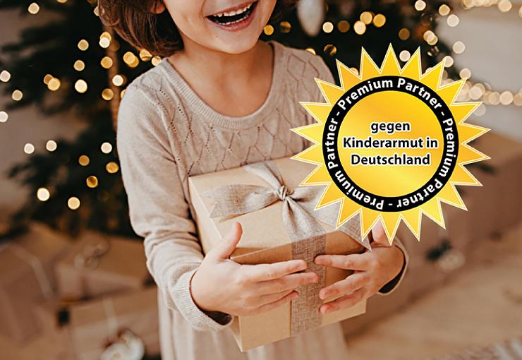 Bild von einem lachenden Kind mit Geschenk vor einem beleuchteten Weihnachtsbaum