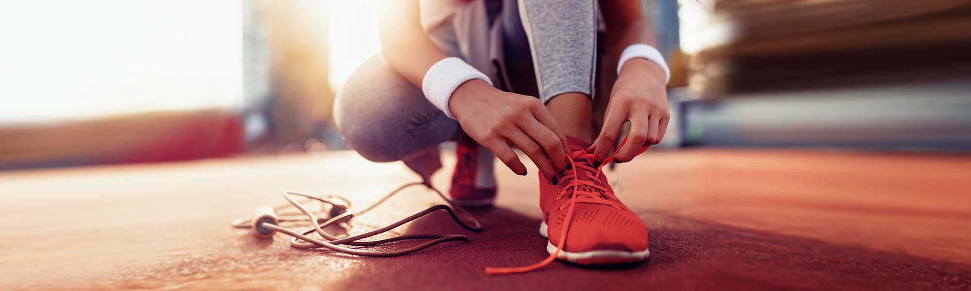 Bild von einer Sportlerin, die gerade ihren roten Laufschuh schnürt