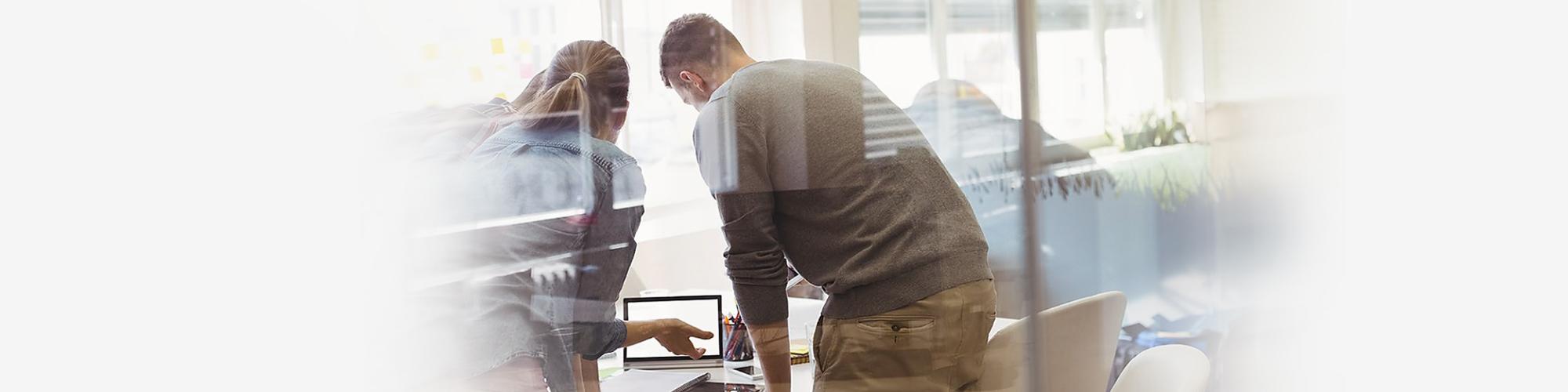 Bild einer Besprechungsszene vor einem Laptop in einem modernen Office