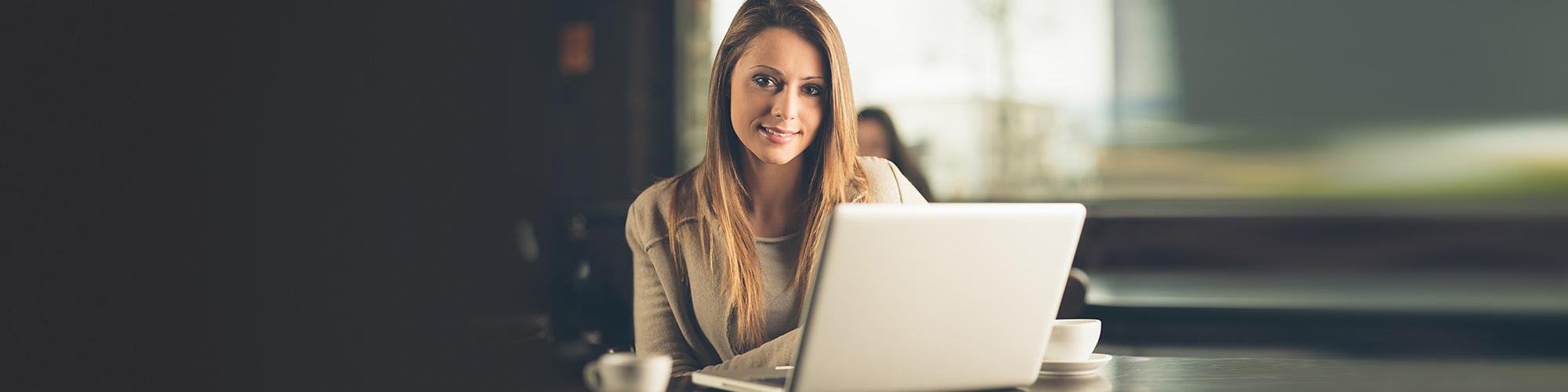 Bild von einer entspannten Schreibtischszene mit Laptop, Kaffee und Grünpflanze - auf dem Monitor ein Mann und eine Frau beim digitalen Expertentalk