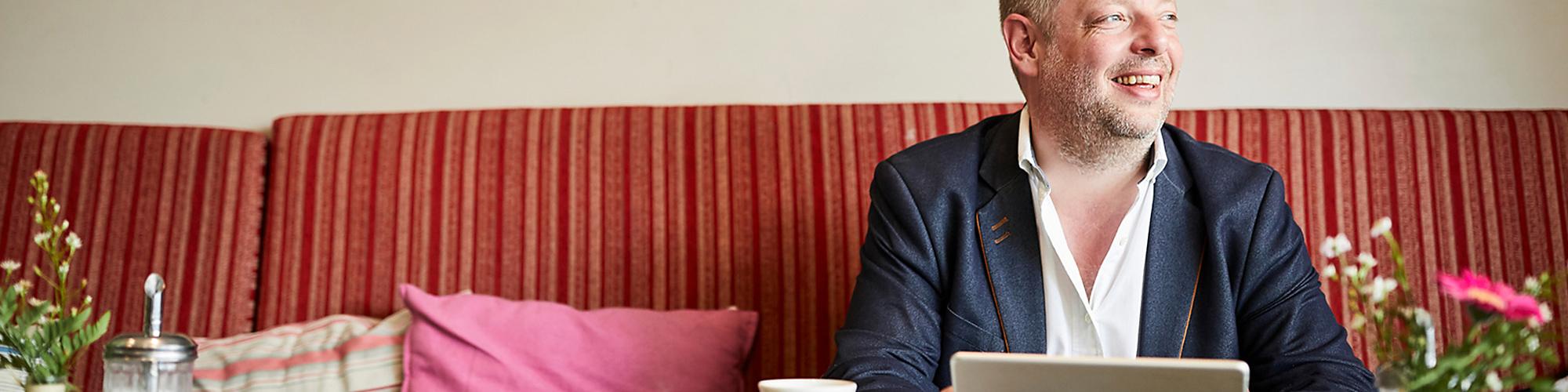 Bild von einem lächelnden Mann mit Laptop und Kaffeetasse