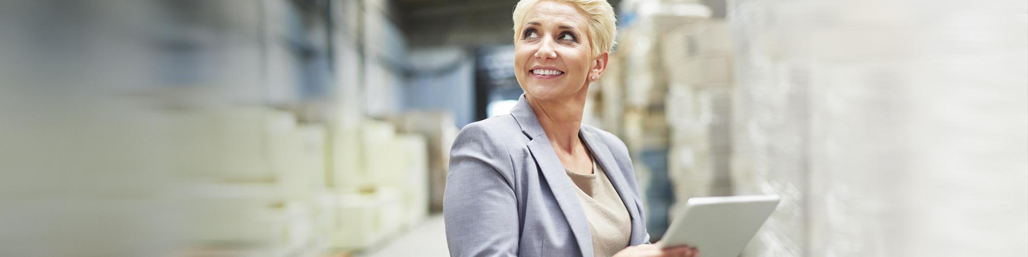 Sage 100 Vorteilsaktion zum Jahresende: Bild einer lächelnden Sage-Anwenderin mit Tablet in einer Lagerhalle