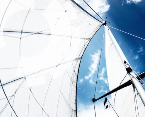 Bild von im Wind aufgeblasenen Segeln mit Blickrichtung nach oben zum blauen Himmel