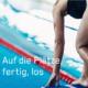 """Bild von einer Schwimmerin, die in Startposition auf einem Springblock steht – dazu die Headline """"Auf die Plätze, fertig, los"""""""