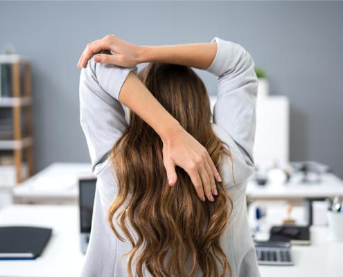 Bild einer Frau im Office, die gerade Dehnungsübungen mit den Armen macht