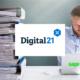 Bild vom Logo Digital21, dem Sage 100 Logo und einem Mann am Laptop, der einen Stapel Aktenordner von sich schiebt