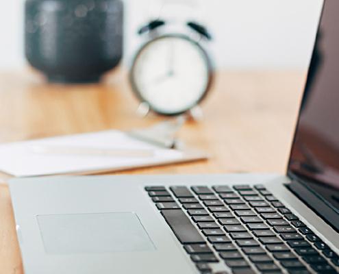 Bild einer Schreibtischszene mit Laptop und einem Wecker im Hintergrund