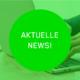 """Grüner Button mit dem Text """"Aktuelle News!"""" im Hintergrund ein Bild von tippenden Händen am Laptop"""