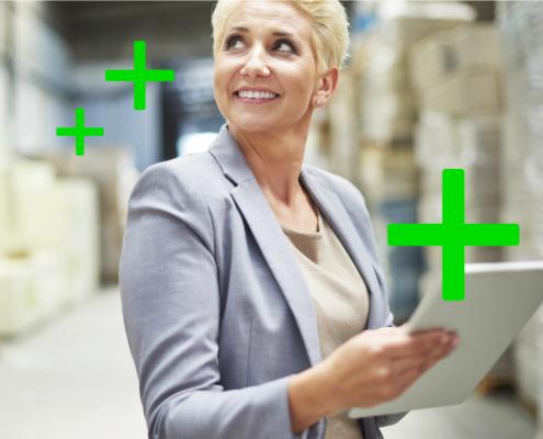 Bild einer lächelnden Sage-Anwenderin mit Tablet in einer Lagerhalle